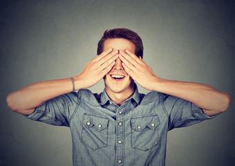 Surprised man covering his eyes smiling