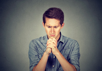 Man thinking and praying with eyes closed