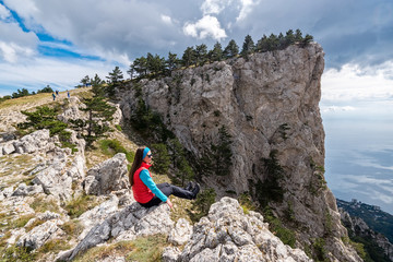 Girl sits on the edge of the cliff