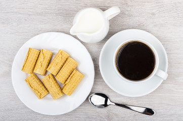 Black coffee, milk jug and rolls wafers in plate