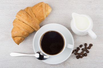 Coffee, croissant, milk jug and coffee beans on table