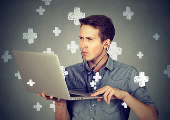 Man listening computer with stethoscope looking at pc laptop.