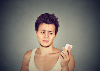 annoyed man holding cellphone looking mad at stressful texts