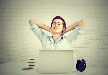 Relaxed man with laptop sitting at desk brick wall background