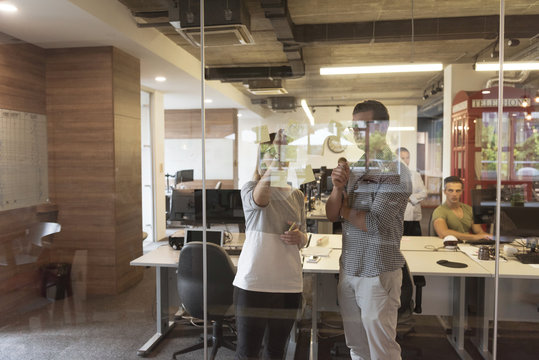 young couple at modern office interior writing notes on stickers