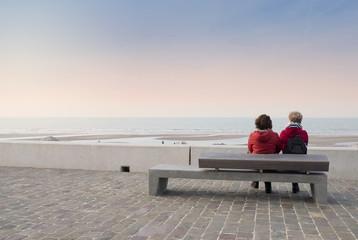 femmes assises sur un banc contemplant le coucher de soleil