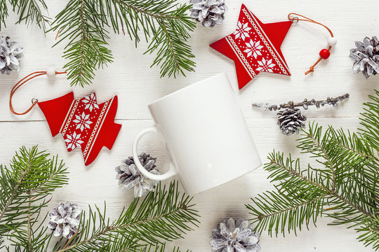 White coffee mug with Christmas decorations and fir branches. Sp