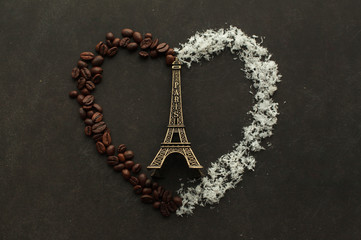 Eiffel tower in a heart made from coffee beans and coconut chips on the dark background with free space to write down.