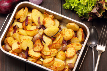 Baked potatoes in a roasting pan with garlic