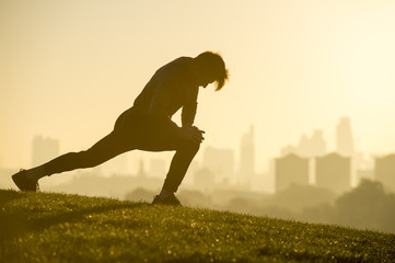 Male jogger stretching on the grassy top of Primrose Hill in front of a misty golden sunrise view of the London city skyline