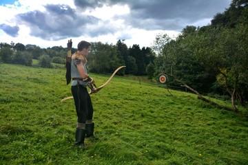 Junger Mittelalterliche Bogenschütze von der Seite  , zielt mit Pfeil und Bogen auf Strohscheibe in grüner Natur