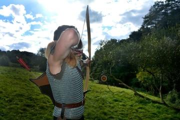 Junger Mittelalterliche Bogenschütze von hinten , zielt mit Pfeil und Bogen auf Strohscheibe in grüner Natur