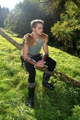 Junger Mittelalterliche Bogenschütze mit Kettenhemd sitzt auf Ast in der Nature im Sonnenlicht und schaut zur Seite
