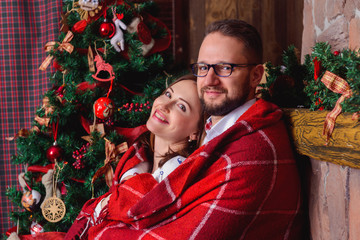 Happy brunette bride and gorgeous groom in the cozy plaid. Christmas tree.