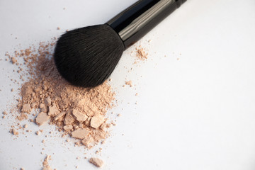 cosmetic brush and flask with powder on a white background