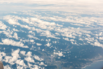 Cloudscape view with mountain above white clouds and blue sky from airplane