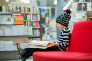 Adorable little child, boy, sitting in a book store
