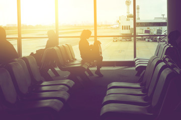 women sit on seat in a lobby airport waiting for flight, soft vi