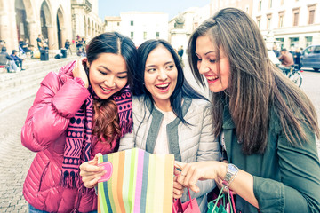 Cheerful girlfriends looking inside shoppers  - Group of young women surprise and joy in a winter  shopping day