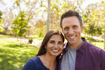 Happy mixed race couple in park looking to camera