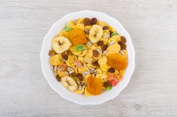 Dry muesli in white glass bowl on wooden table