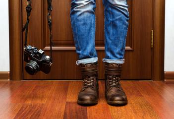 Девушка в кожаных ботинках с фотоаппаратом