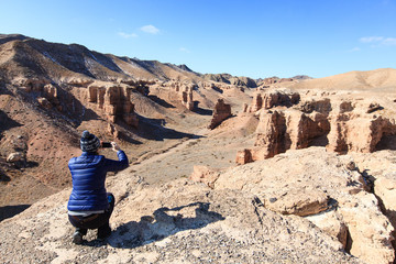 Woman taking pictures on mobile phone in Charyn Canyon in Kazakhstan