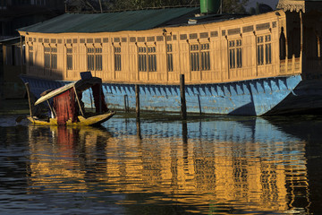 Small shikara transport boat passing a houseboat on Dal Lake at sunset, Srinagar, Kashmir, India,