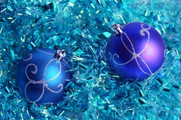 Two christmas balls on the blue tinsel.