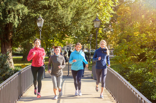 Four young women jogging over bridge