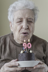 Senior woman with a birthday cake for ninety