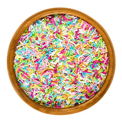 Colorful sugar sprinkles for food decorations in wooden bowl on white background. Multi colored bakery decoration ingredient, used for cakes and cookies. Isolated macro food photo close up from above.