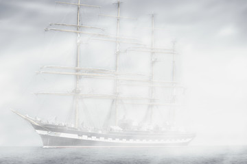 Tall ship regatta in a mist at sea.