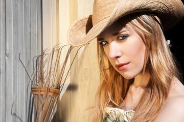 Blonde Female In Western Hat In Front of Barn Door with Rake