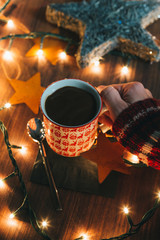 Hands holding a cup of hot chocolate with Christmas lights