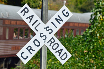 Railroad Crossing sign with an antique steam train in the background