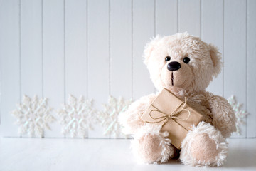 White Christmas background with teddy bear - selective focus, copy space