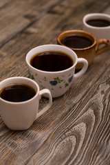Four cups of coffee on wooden background