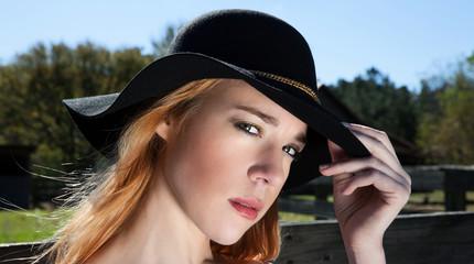 Blonde Female Holding Black Hat Outdoors