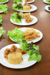 blurred of food, fried rice and breaded fried chicken in white p