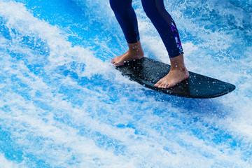 Woman's legs standing on surfboard