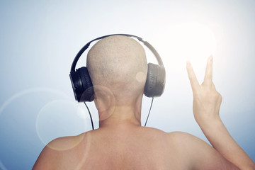 Bald female head with headphones, showing thumbs Victoria. Rear view.