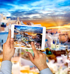 Tourist man taking picture with touch pad in Oia town on Santorini island. Travel concept.  Europe summer travel destination in Greece, Caldera, Aegean sea.