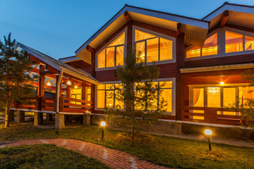 New modern Log Home with Large Porch at dusk