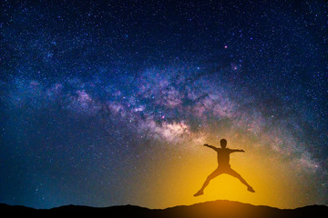 Landscape with Milky way galaxy. Night sky with stars and silhouette jumping man on the mountain.