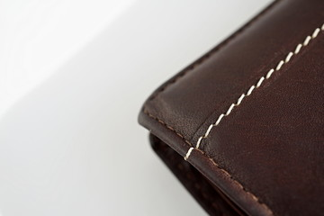 Macro detail of a white and brown thread stitching black and brown stitched leather wallet