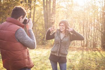 Junge Frau posiert ihrem Freund im Park für ein Foto