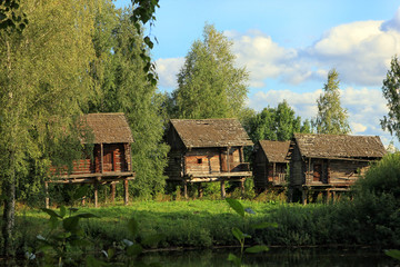 beautiful old Russian wooden log huts on wooden stilts in the vi