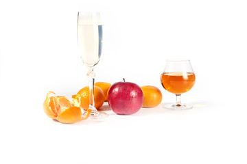 fresh apple and tangerine on the table next to the wine glasses