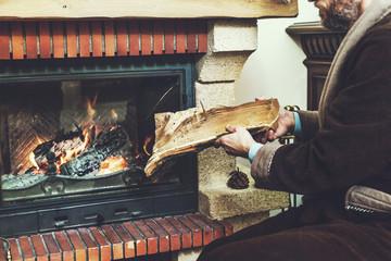 man with beard wearing bathrobe puts log in burning fireplace